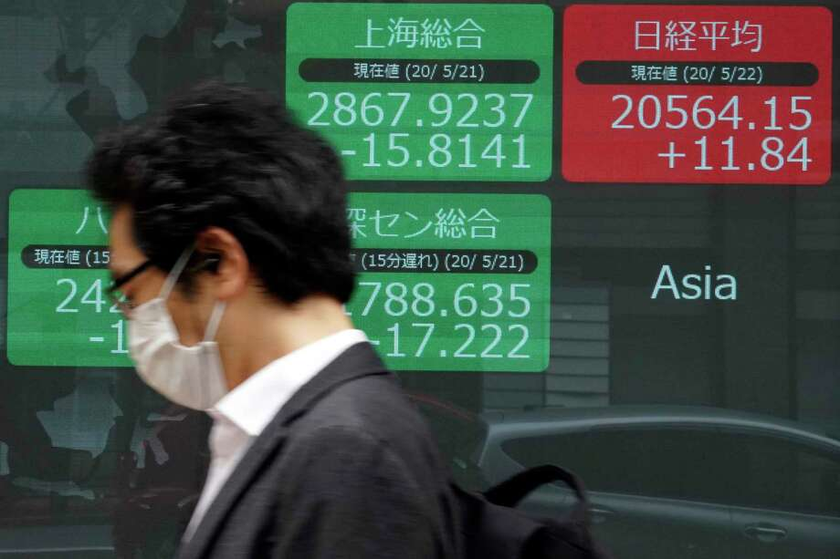 A man walks past an electronic stock board showing Japan's Nikkei 225 and other Asian indexes at a securities firm in Tokyo Friday, May 22, 2020. Photo: Eugene Hoshiko / Copyright 2020 The Associated Press. All rights reserved