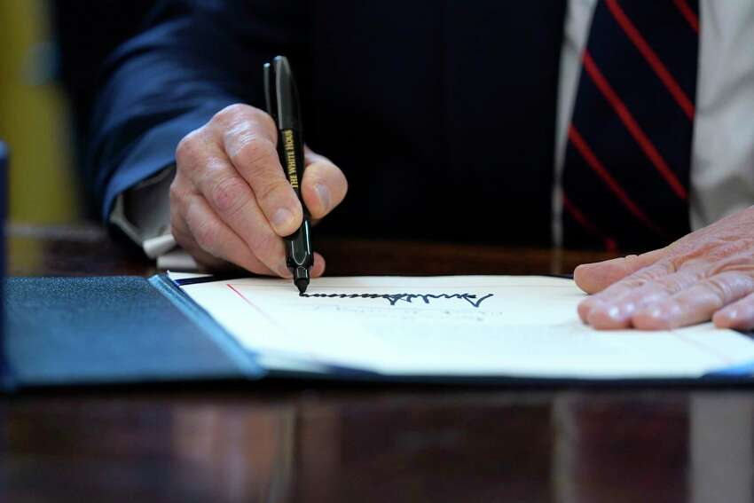 FILE - In this March 27, 2020 file photo, President Donald Trump signs the coronavirus stimulus relief package in the Oval Office at the White House in Washington. Economic stimulus checks have already begun hitting some bank accounts a€?