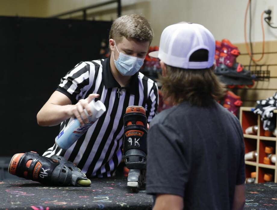 Logan Rogers sanitizes skates for Carson Perez at Rainbow Roller Rink, Friday, May 22, 2020, in Conroe. The business reopened to customers Friday with social distancing and other guidelines under Gov. Greg AbbottÕs phased reopening of the economy. Photo: Jason Fochtman/Staff Photographer / 2020 ? Houston Chronicle