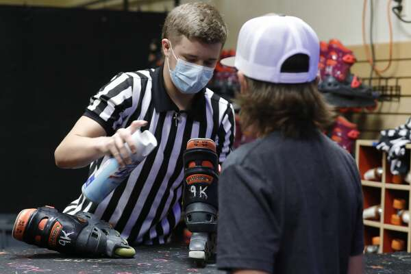 Logan Rogers sanitizes skates for Carson Perez at Rainbow Roller Rink, Friday, May 22, 2020, in Conroe. The business reopened to customers Friday with social distancing and other guidelines under Gov. Greg Abbott?•s phased reopening of the economy.