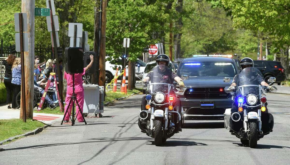 Because of the pandemic the Mary Wade Parade was different this year. A New Haven Police escort leads a car parade honoring residents and staff at the Mary Wade Home as it passes the nursing home and assisted living facility on Pine Street in New Haven in May 2020.