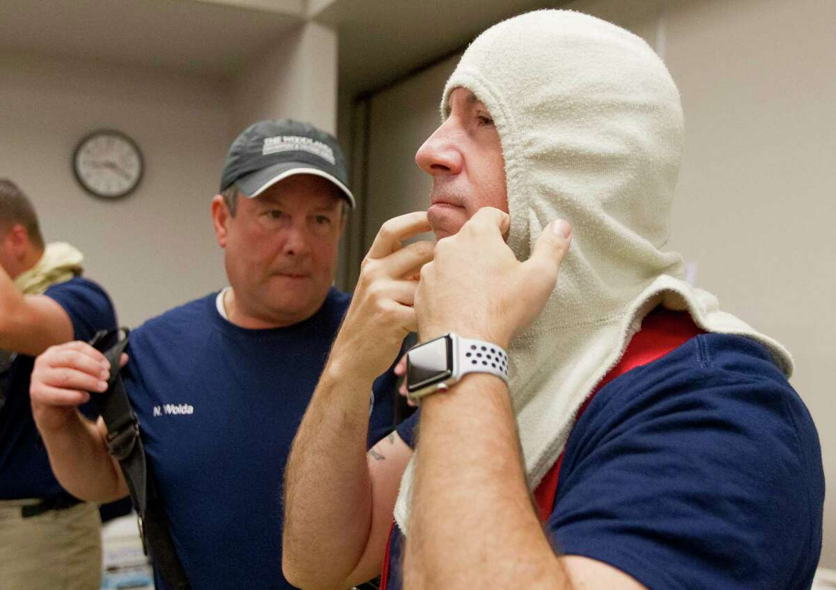 John Anthony Brown, board member with The Woodlands Township, puts on a protective hood beside Nick Wolda, president of Visit The Woodlands, as community leaders took part in FireOps 101, Friday, May 31, 2019, in The Woodlands. The event gave participants a first-hand taste of what members of The Woodlands Fire Department and other firefighters go through as part of their job. Brown will seek a third term in office, he confirmed on May 22, 2020.