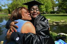 """Nancy Green, right, hugs her best friend, Barbara Morris, both of Stamford, as she dons her cap and gown for her graduation from Southern Connecticut University May 21, 2020. Green, who calls Morris her """"one woman cheering squad,"""" is recovering from a serious case of COVID-19 that threatened her life in March."""
