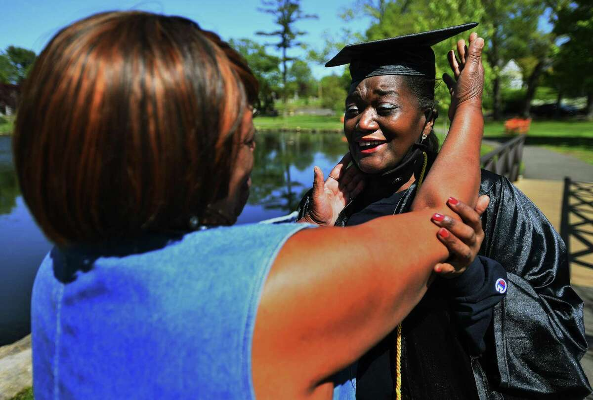 Nancy Green, right, hugs her best friend, Barbara Morris, both of Stamford, as she dons her cap and gown for her graduation from Southern Connecticut University May 21, 2020. Green, who calls Morris her