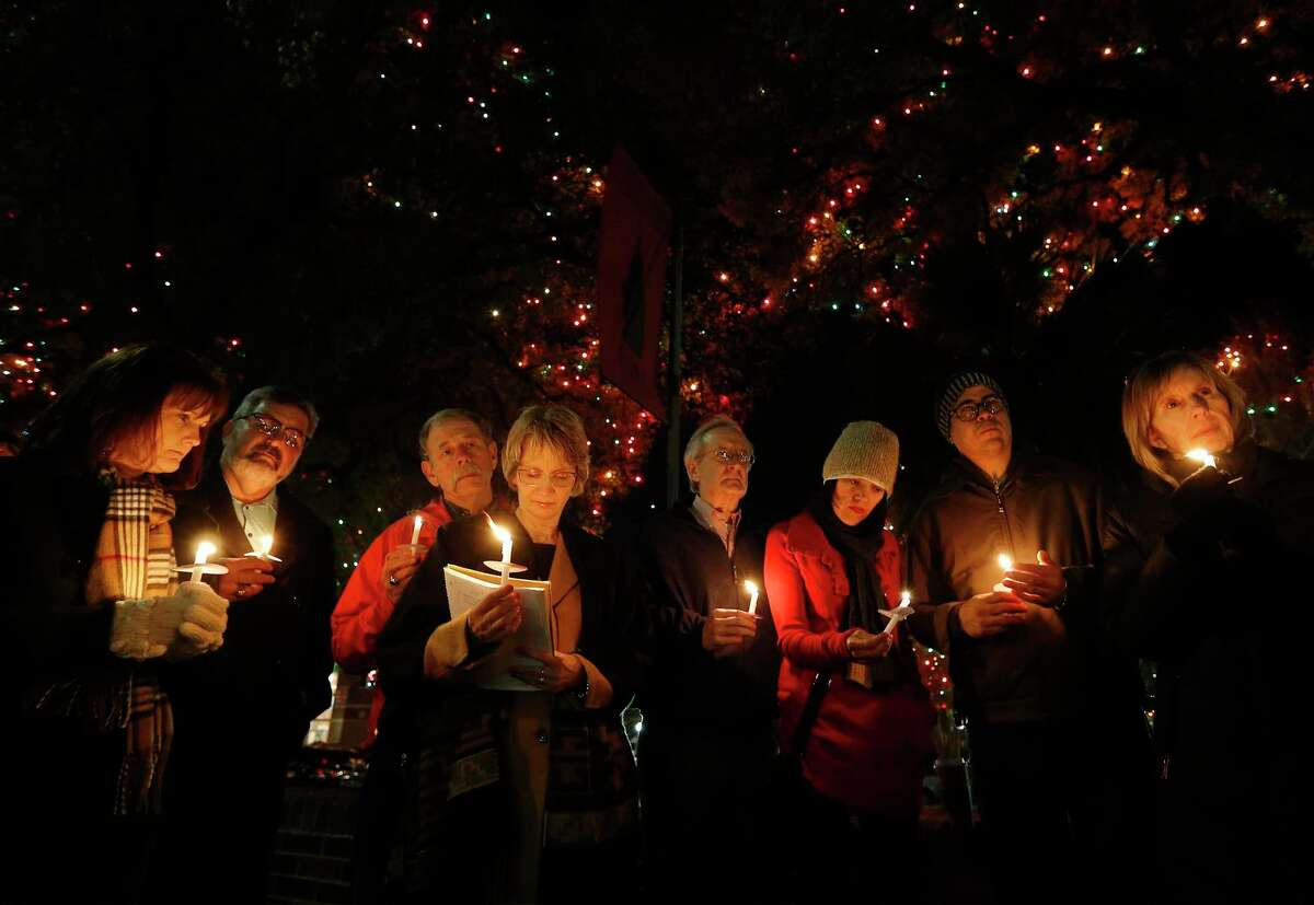 Valerie Redus (fourth from left) and her husband, Mickey (third from left), join others in a candlelight vigil in front of the University of the Incarnate Word on Dec. 6, 2016, to mark the three-year anniversary of the death of their son, Cameron. He was a student at UIW who was shot five times by a campus police officer. About 40 people gathered for the vigil, many of them Cameron's classmates. (Kin Man Hui/San Antonio Express-News)
