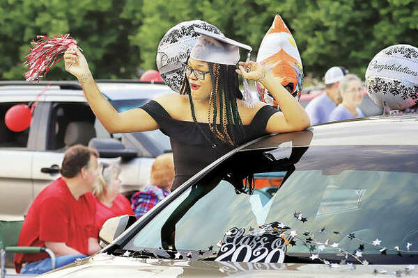 A proud and confident member of the Alton High School Class of 2020 shows off for friends Friday night during the school's drive-through Graduation Parade held near the Alton riverfront. Hundreds of cars lined up for the procession which passed cheering families, friends and classmates.