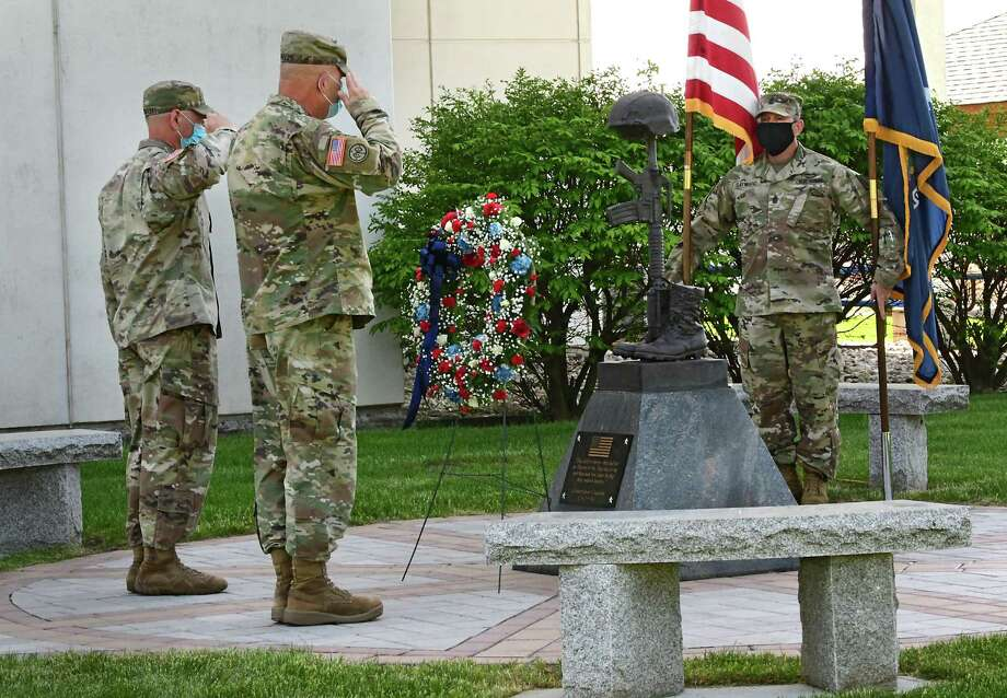New York State Command Sergeant Major David Piwowarski, left, and Major General Ray Shields salute after carrying a wreath to a memorial statue during a traditional Memorial Day ceremony at New York State Division of Military and Naval Affairs Headquarters on Friday, May 22, 2020 in Latham, N.Y. Sergeant Major Roy Sayward is seen holding the United States and New York State flags at right. (Lori Van Buren/Times Union) Photo: Lori Van Buren / 40049353A