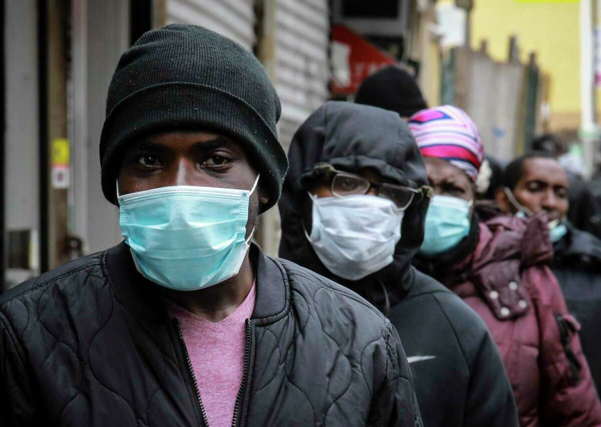 """People wait for a distribution of masks and food from the Rev. Al Sharpton in the Harlem neighborhood of New York, after a new state mandate was issued requiring residents to wear face coverings in public due to the COVID-19 coronavirus, Saturday, April 18, 2020. """"Inner-city residents must follow this mandate to ensure public health and safety,"""" said Sharpton. The latest Associated Press analysis of available data shows that nearly one-third of those who have died from the coronavirus are African American, even though blacks are only about 14% of the population."""