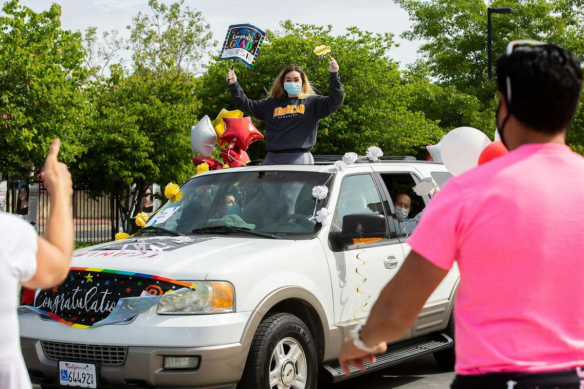 Alexis Boss celebrates as her names is called out over a speaker as she enters the parade at Carondelet High School on Saturday, May 16, 2020, in Concord, Calif. The all-girls private Catholic school hosted a drive-thru parade for their graduating class of 2020.