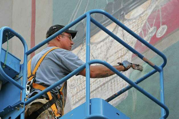 Muralist Kevin Clark works on a mural of the Troy Savings Bank Music Hall above the parking lot adjacent to the music hall and bank in Troy.  (Lori Van Buren / Times Union) Photo: Lori Van Buren