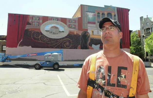 Muralist Kevin Clark in front of the mural he painted of the Troy Savings Bank Music Hall above the parking lot adjacent to the music hall and bank in Troy.  (Lori Van Buren / Times Union) Photo: Lori Van Buren