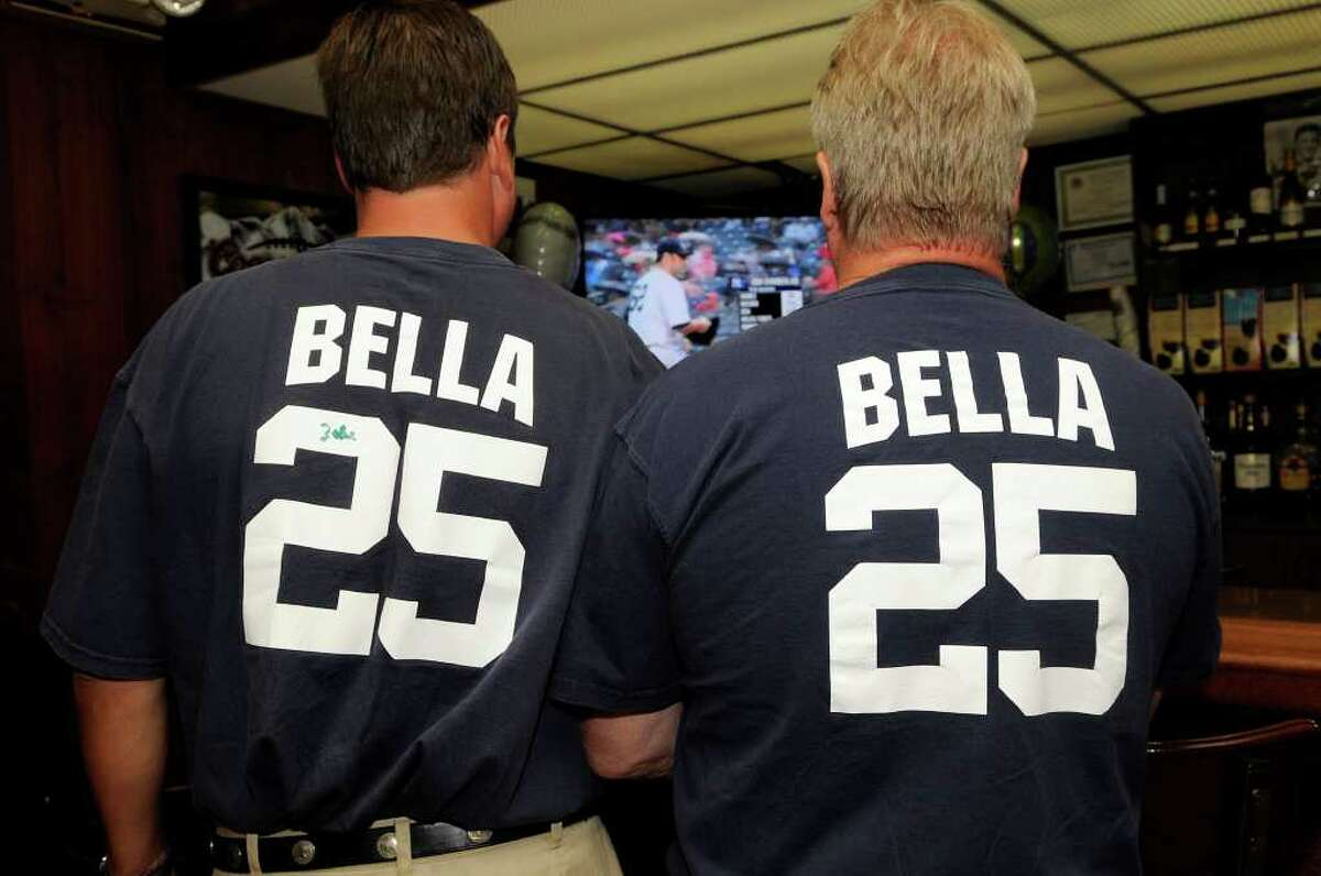 Thaddeus Kochan, Cos Cob, left, and Chip Smith, Old Greenwich, watch a Yankee game while wearing the Yankee jersey number of their friend, John