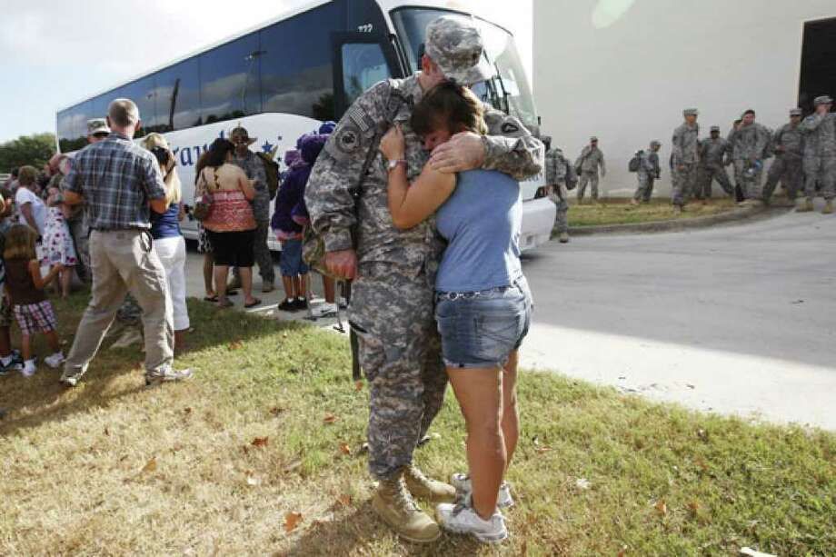 Spc. Daniel Mills hugs his wife, Kat, as family members gather in Seguin's Central Park to welcome 90 soldiers from the U.S. Army National Guard Alpha Battery, 1-133 Field Artillery, home from a tour of duty in Iraq.