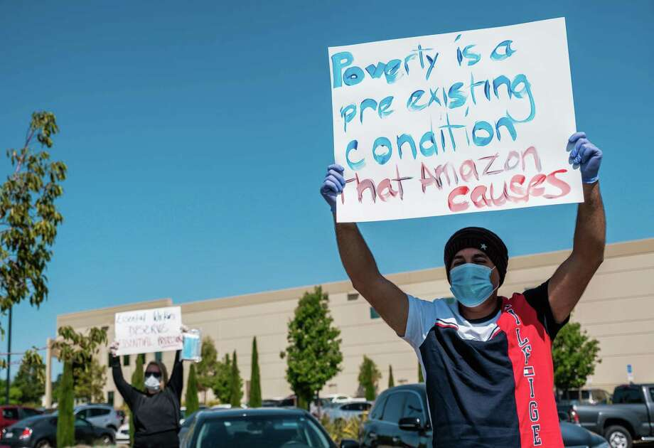 Al Aloudi, who drives for Amazon Flex, holds up a sign while protesting at an Amazon distribution center. A small group of people, some of them Amazon employees, gathered to demand better wages and better protections against the coronavirus. Photo: Photo For The Washington Post By Nick Otto. / Nick Otto