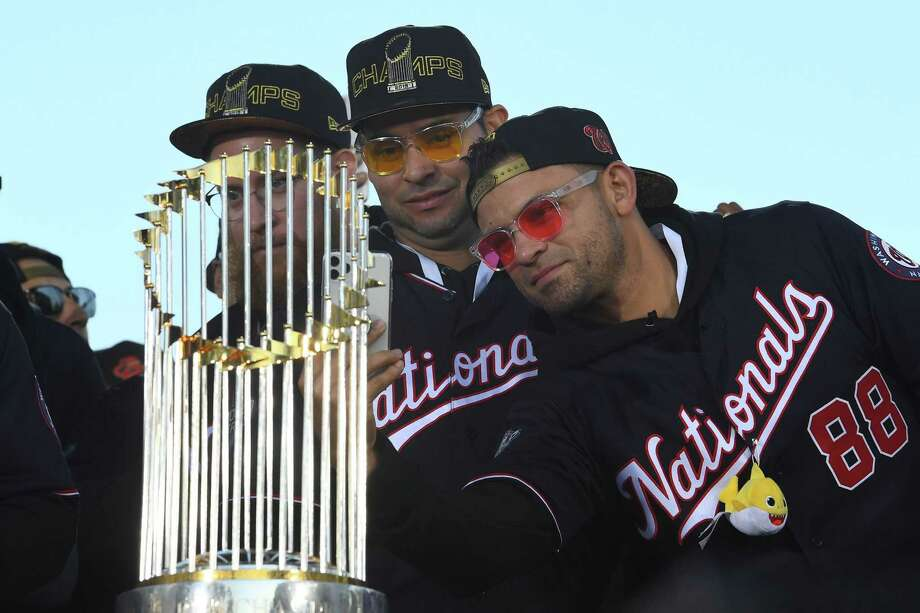 Sean Doolittle, Aníbal Sánchez (19) and Gerardo Parra (88) check out the Commissioner's Trophy during the Nationals' parade on Nov.. 2, 2019. Photo: Washington Post Photo By Katherine Frey. / The Washington Post