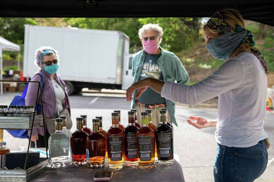 Jaime Windon, the CEO and founder of Windon Distilling, sells her rum to Doyle Niemann and his wife Karen Morrill at the Riverdale Park Farmers Market in Riverdale Park, Md. Photo: Photo For The Washington Post By Amanda Andrade-Rhoades. / Amanda Andrade-Rhoades