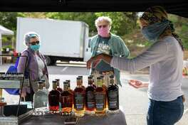 Jaime Windon, the CEO and founder of Windon Distilling, sells her rum to Doyle Niemann and his wife Karen Morrill at the Riverdale Park Farmers Market in Riverdale Park, Md.