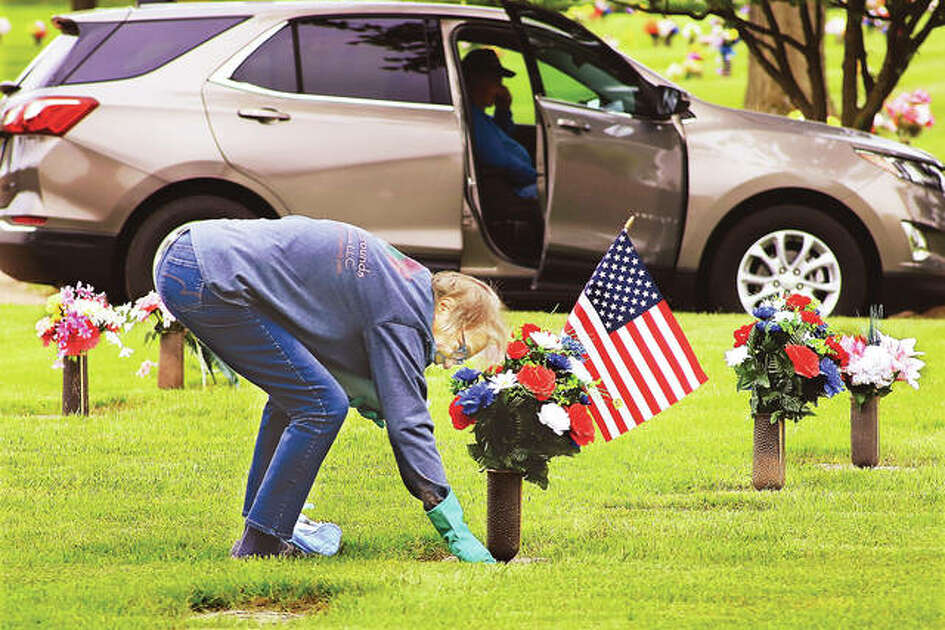 Helen Hickam of Edwardsville wipes off the grave stone Thursday of her mother and father at Rose Lawn Memory Gardens cemetery in Bethalto. Hicham was decorating the grave as many people have already done across the area in advance of Memorial Day on Monday. Public health concerns this year have silenced many of the traditional Memorial Day services.