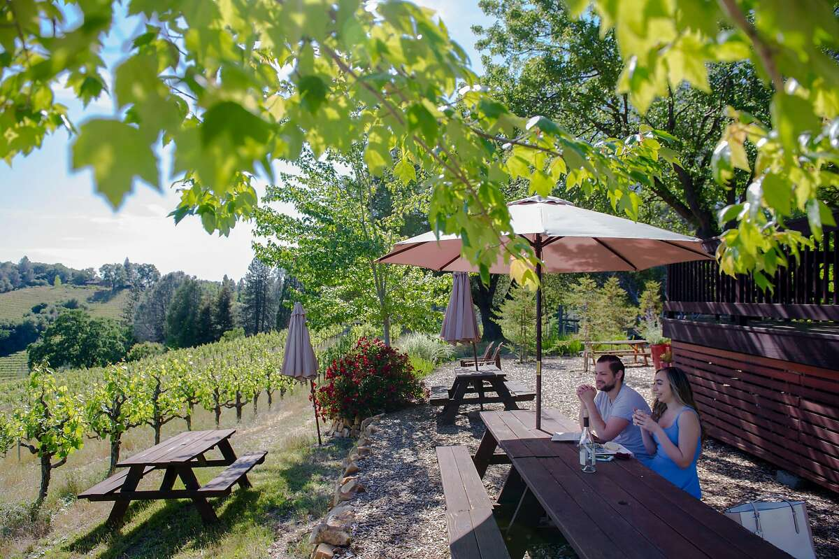 Sean Stoyanowski and Bianca Rusconi, both of Sacramento, have wine and food at Holly's Hill Vineyards in Placerville, Calif. on Friday, May 22, 2020.