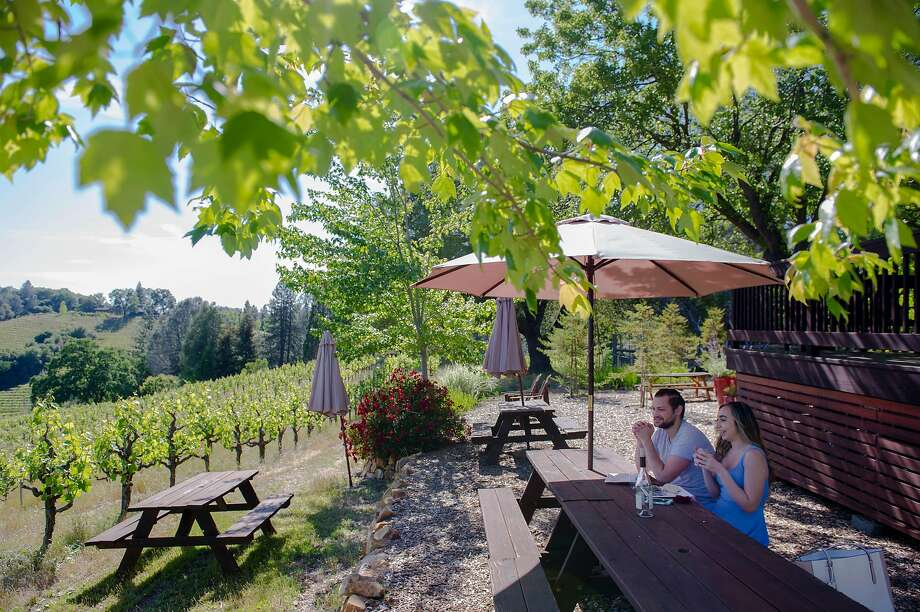 Sean Stoyanowski and Bianca Rusconi, both of Sacramento, have wine and food at Holly's Hill Vineyards in Placerville. Photo: Chris Kaufman / Special To The Chronicle