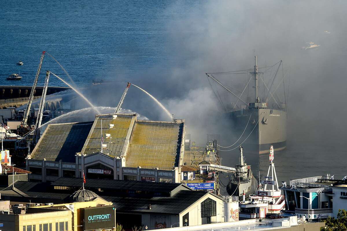 Smoke rises from Pier 45 as a fire burns on Saturday, May 23, 2020, in San Francisco. At right is the SS Jeremiah O'Brien.