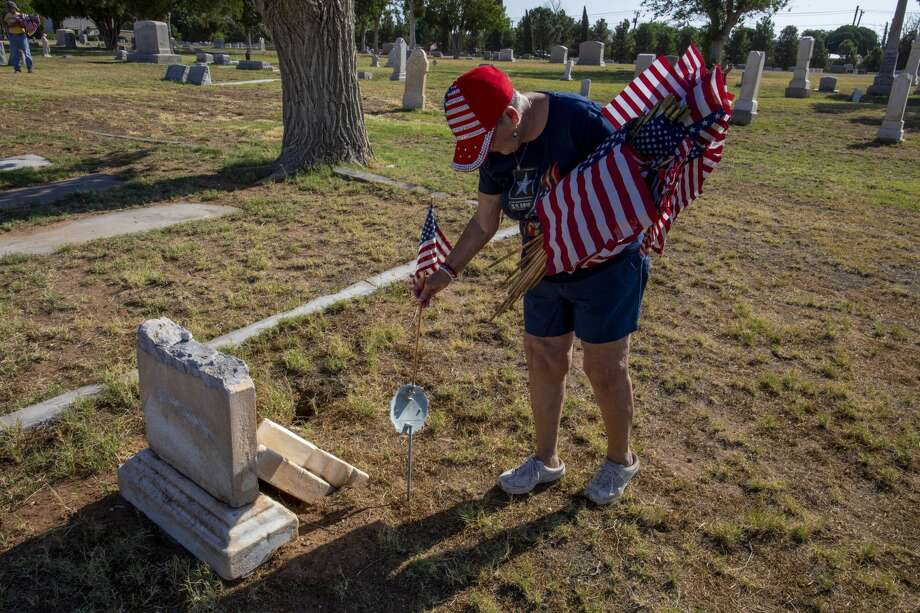 Karyn Basse places a flag on a veteranÕs grave Saturday, May 23, 2020 at Fairview Cemetery. Jacy Lewis/Reporter-Telegram Photo: Jacy Lewis/Reporter-Telegram