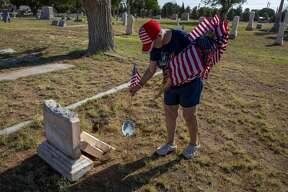 Karyn Basse places a flag on a veteran?•s grave Saturday, May 23, 2020 at Fairview Cemetery. Jacy Lewis/Reporter-Telegram