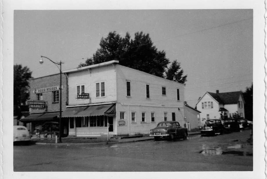 Corner of Clark St. and Benzie Boulevard, in Beulah early 1950's, showing the Crystal Bakery and Crawford's Market food store. (Courtesy Photo)