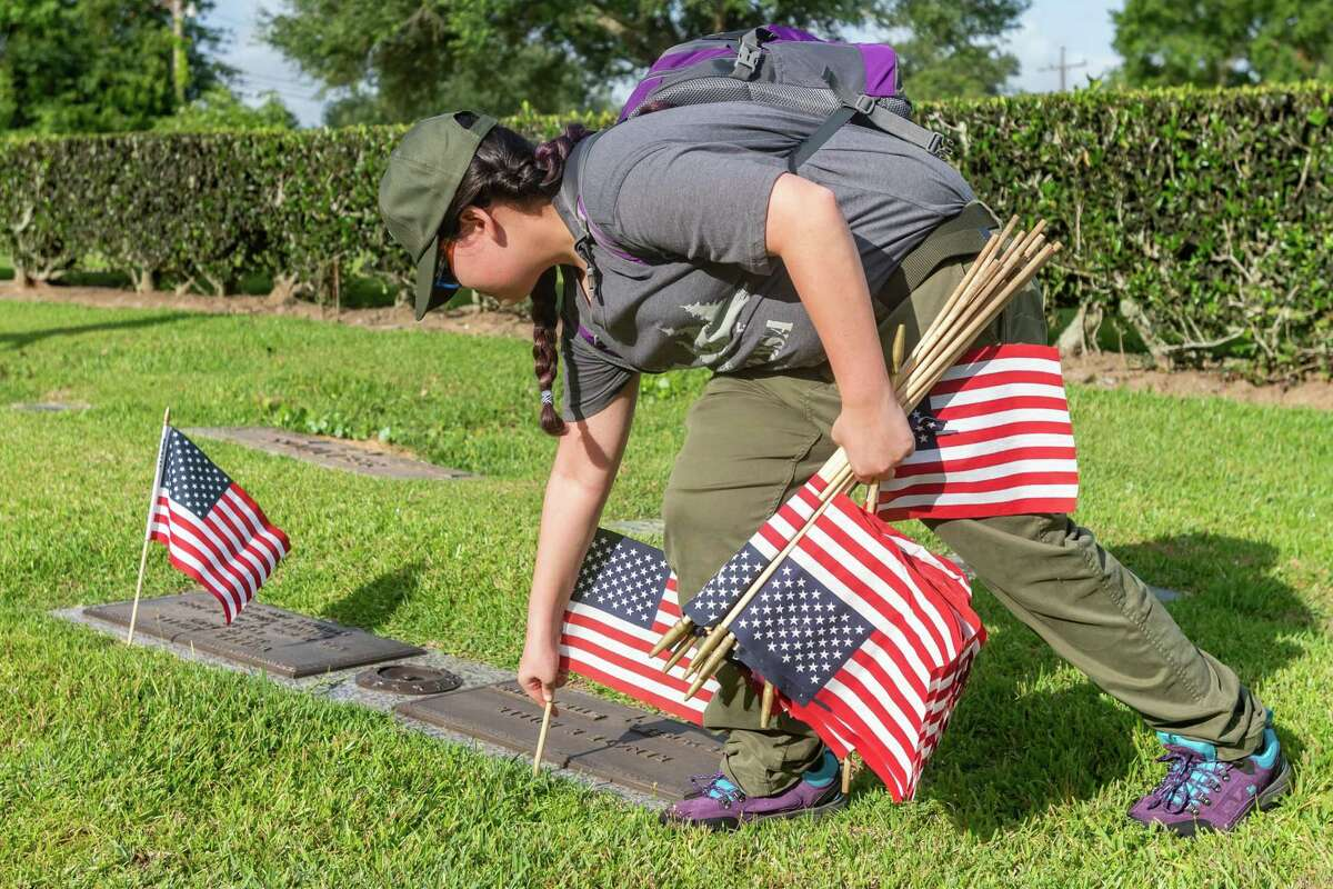 Kadi Gutierrez, 11, of Troop 1981 places a couple of flags near headstones. To honor our veterans on Memorial Day, members of five area scout troops combined their efforts to place about 6000 flags on the graves of veterans at Forest Lawn Memorial Park on Saturday morning. Photo made on May 23, 2020. Fran Ruchalski/The Enterprise