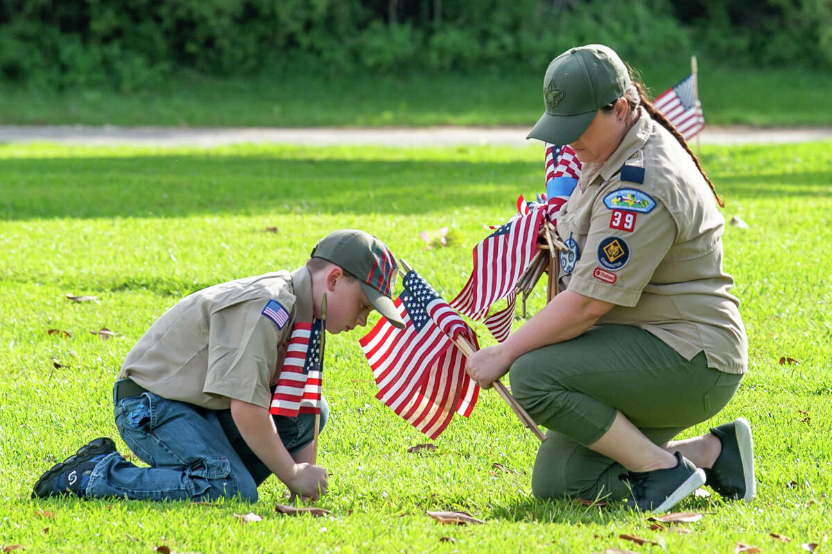 Jacob Bronson, 9, gets an assist from Cubmaster Leigh-Ann Bronson in placing a flag. To honor our veterans on Memorial Day, members of five area scout troops combined their efforts to place about 6000 flags on the graves of veterans at Forest Lawn Memorial Park on Saturday morning. Photo made on May 23, 2020. Fran Ruchalski/The Enterprise