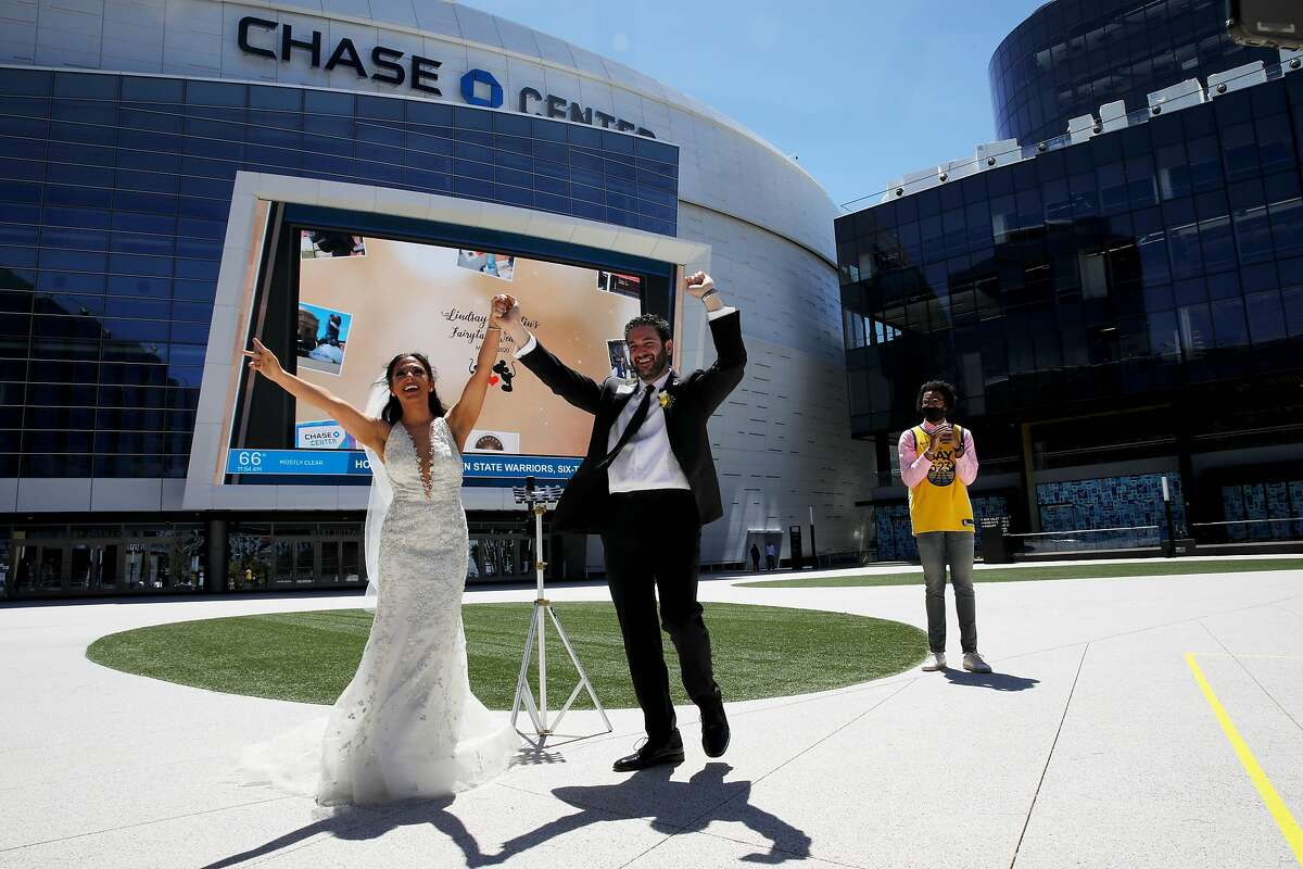 Lindsay and Dustin Schneider celebrate during their wedding at the Chase Center, with Golden State Warriors rookie Jordan Poole as their witness in San Francisco, Calif., on Saturday, May 23, 2020. Rebeca Delgadillo (CQ'D) officiated the ceremony. The couple had been scheduled to get married on May 23 in Orlando (big Disney fans). Due to coronavirus those plans were scrapped, so they approached the Warriors about getting married outside Chase. The Warriors said yes.