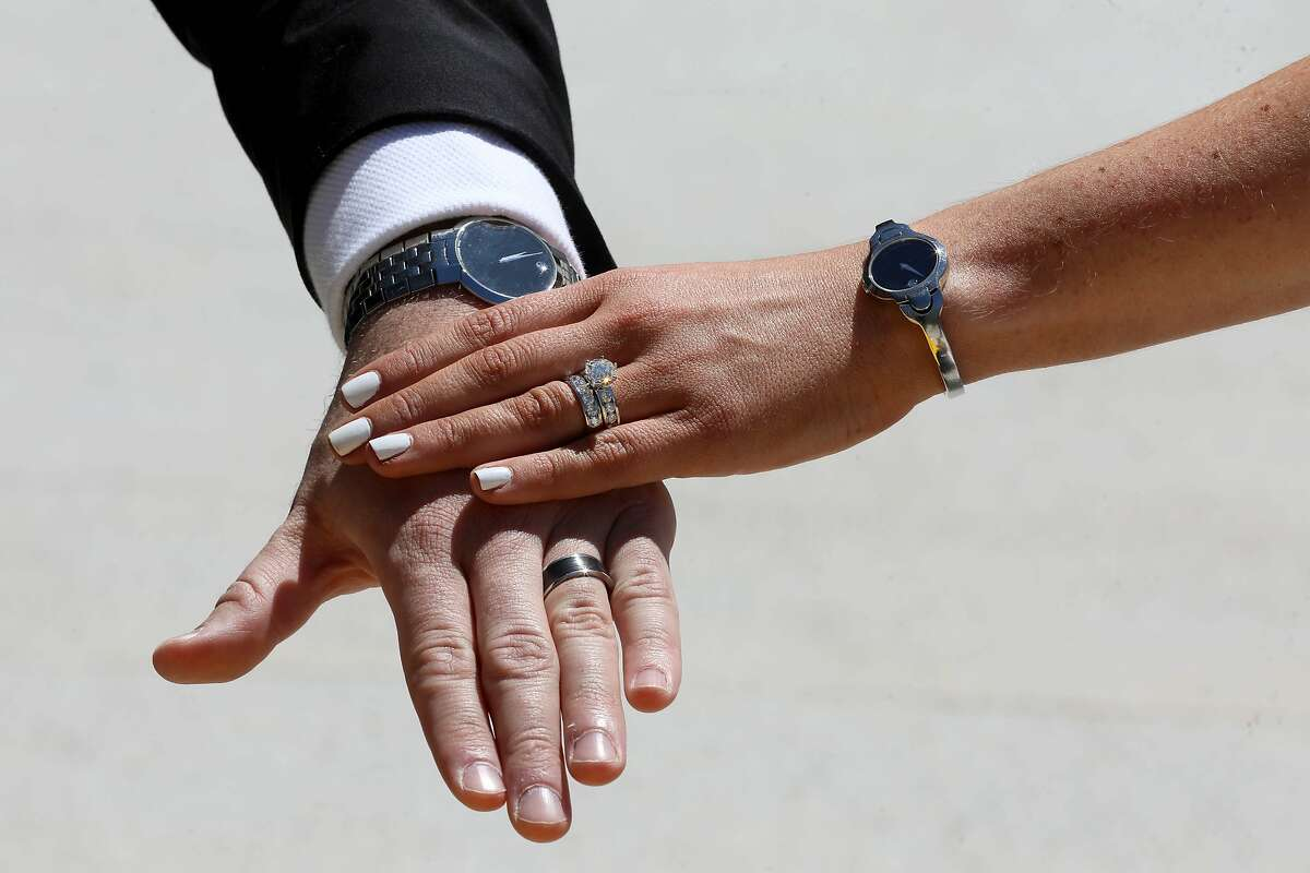 Lindsay and Dustin Schneider show off their wedding rings following their marriage ceremony at the Chase Center, with Golden State Warriors rookie Jordan Poole as their witness in San Francisco, Calif., on Saturday, May 23, 2020. Rebeca Delgadillo (CQ'D) officiated the ceremony. The couple had been scheduled to get married on May 23 in Orlando (big Disney fans). Due to coronavirus those plans were scrapped, so they approached the Warriors about getting married outside Chase. The Warriors said yes.