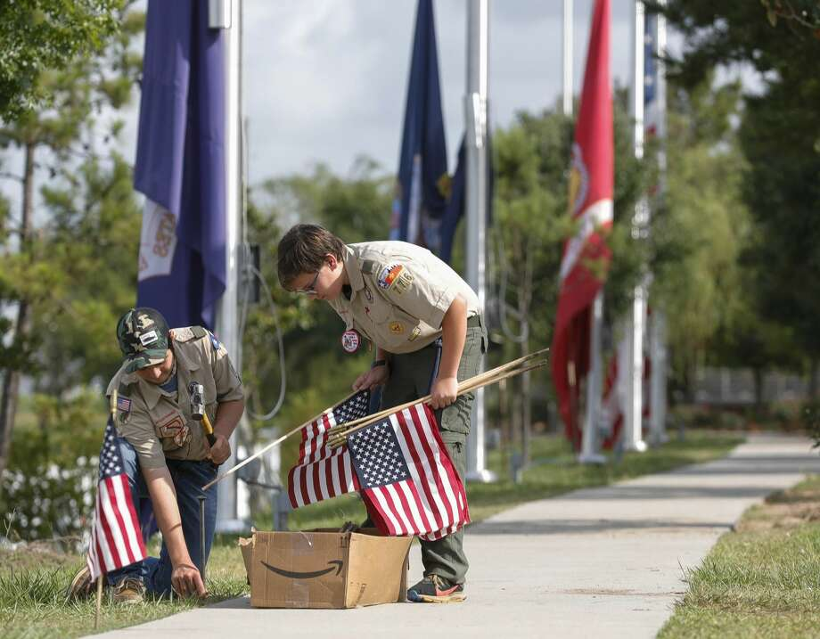 Kannon Rivero, left, and Ryland Saltzman, Boy Scouts with Troop 776, install American flags along the pathway at the Montgomery County Veterans Memorial Park, Saturday, May 23, 2020, in Conroe. Scouts, veterans and other volunteers installed flags along the path around the park, as well as help change out several service flags prior to Memorial Day on Monday. Photo: Jason Fochtman/Staff Photographer / 2020 ? Houston Chronicle