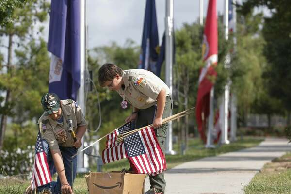 Kannon Rivero, left, and Ryland Saltzman, Boy Scouts with Troop 776, install American flags along the pathway at the Montgomery County Veterans Memorial Park, Saturday, May 23, 2020, in Conroe. Scouts, veterans and other volunteers installed flags along the path around the park, as well as help change out several service flags prior to Memorial Day on Monday.