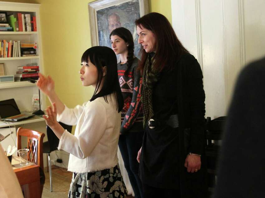 CAMBRIDGE, MA - FEBRUARY 5: Marie Kondo, zen tidiness guru speaks in Japanese through an interpreter tells Claduia Logan and her daughter Otti,16, there is much joy in their dining room/ office. (Photo by Joanne Rathe/The Boston Globe via Getty Images)