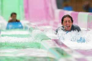 Ethan Marx, center, shares a laugh after racing friends and family down a water slide at Big Rivers Waterpark, Saturday, May 23, 2020, in New Caney. The waterpark open for the season following Gov. Greg Abbott's start of Phase 2 reopening of the economy that began Friday.