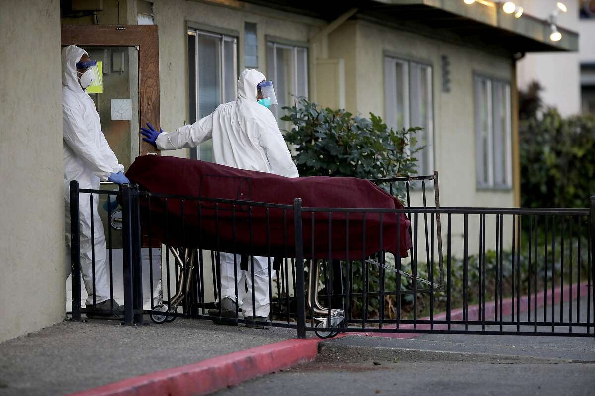 Men donning hazmat suits bring a body out of Gateway Care and Rehabilitation, located at 26660 Patrick Ave., on Wednesday, April 8, 2020, in Hayward, Calif. Six residents at the skilled nursing home in Hayward have died after being infected by the coronavirus in an outbreak at the facility that has infected 29 other residents and 24 staff members. Alameda County public health spokeswoman Neetu Balram confirmed the outbreak Wednesday afternoon.Officials are also monitoring an outbreak at East Bay Post-Acute Rehab in Castro Valley where seven people, including four staffers, have tested positive. Balram cautioned the number of infected persons at each facility could be updates and should be considered a