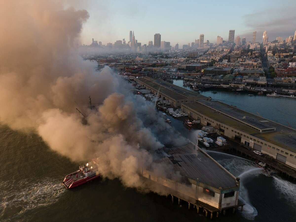 Firefighters spray water on Pier 45 4-alarm that began in the warehouse early on Saturday, May 23, 2020, in San Francisco, Calif. The SS Jeremiah O'Brien is docked next to this pier.