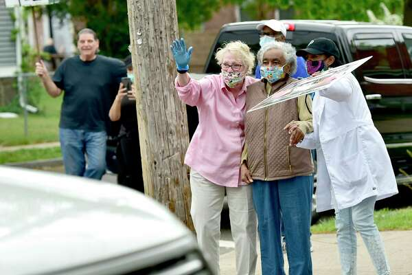 New Haven, Connecticut - Saturday, May 23, 2020: Friend Peggy Gras of West Hartford, second from left, former New Haven Alder Andrea Jackson-Brooks, third from left, and caregiver Patty Newton-Foster of New Haven, far right, watch together as a procession of cars and well-wishers show love and affection Saturday for Jackson Brooks for her service to the City of New Haven at the corner of Dewitt and Spring Streets that is renamed Andrea Jackson-Brooks Way where Jackson-Brooks lives.