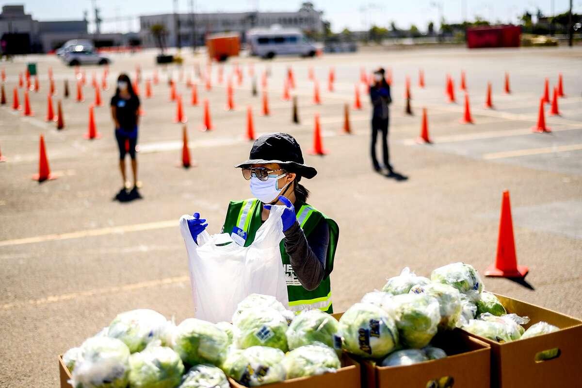 Kesinee Yip, Pa volunteer with the San Francisco-Marin Food Bank, prepares a food bundle on Saturday, May 23, 2020, in San Francisco.