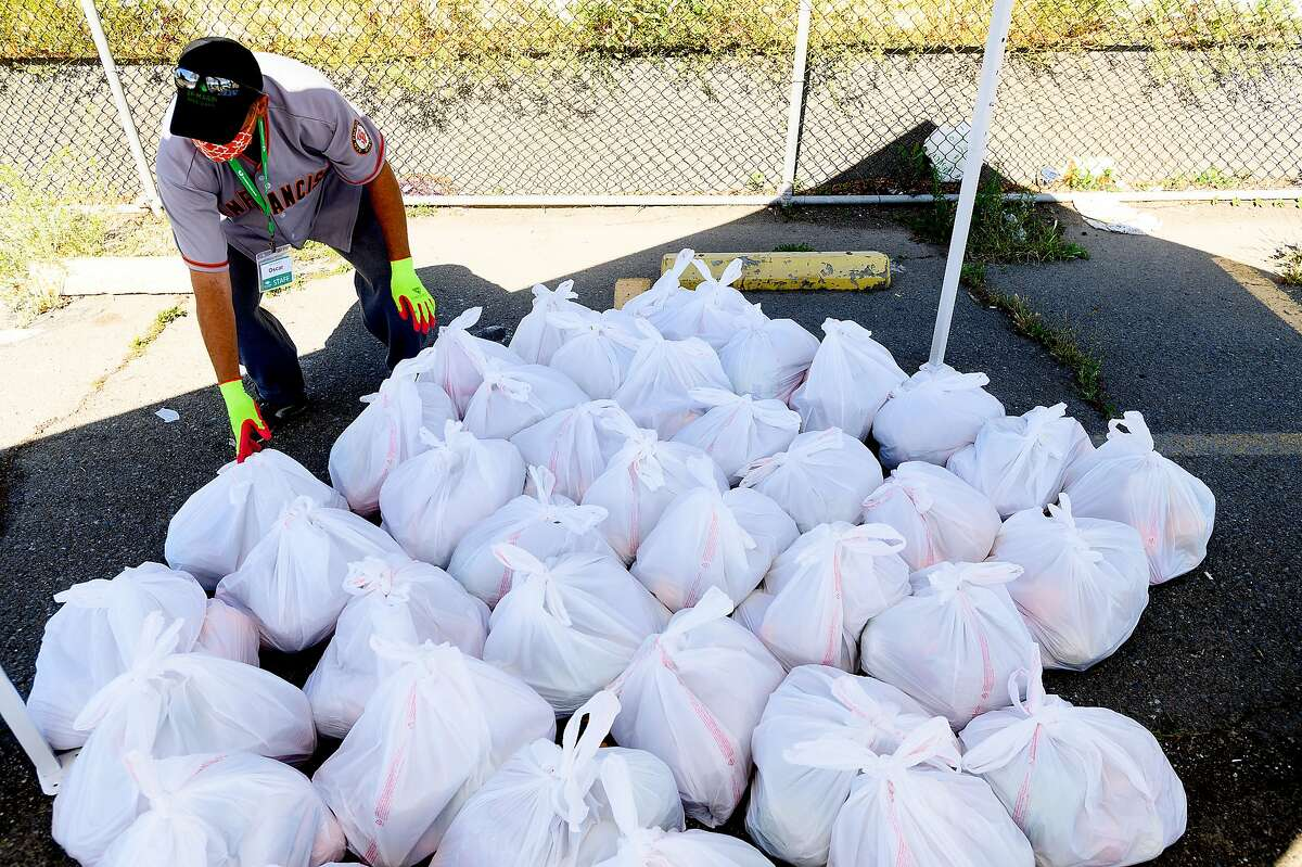 Oscar Platero, a staff member with the San Francisco-Marin Food Bank, sorts food bundles during a distribution event on Saturday, May 23, 2020, in San Francisco.