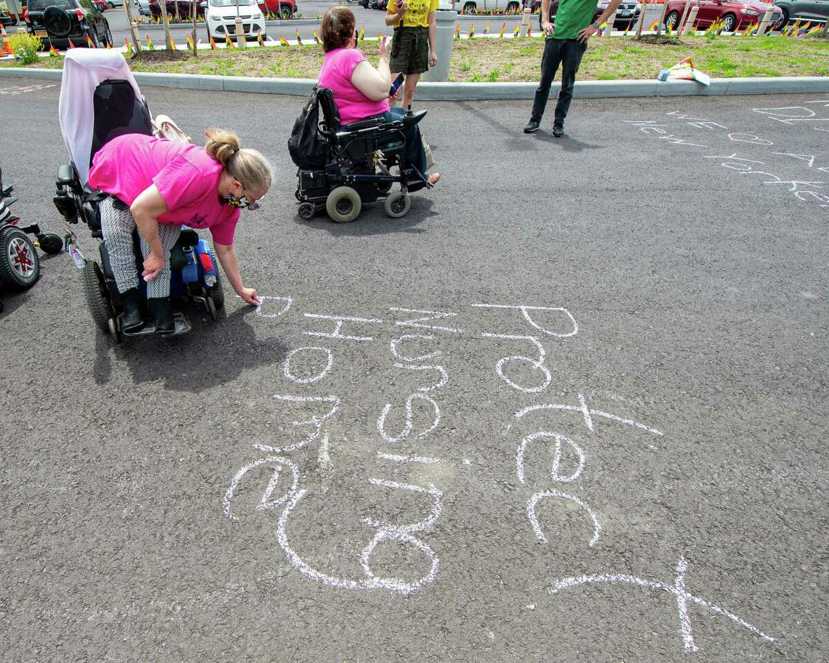 Julie Farrar writes a message on on the driveway leading to the Shaker Place Rehabilitation and Nursing Center in Colonie during a vigil held by ADAPT Capital Region on Saturday, May 23, 2020 calling on New York state to support nursing home workers, transfer residents who so choose to safer settings and step up state regulations of nursing homes (Jim Franco/Special to the Times Union.)