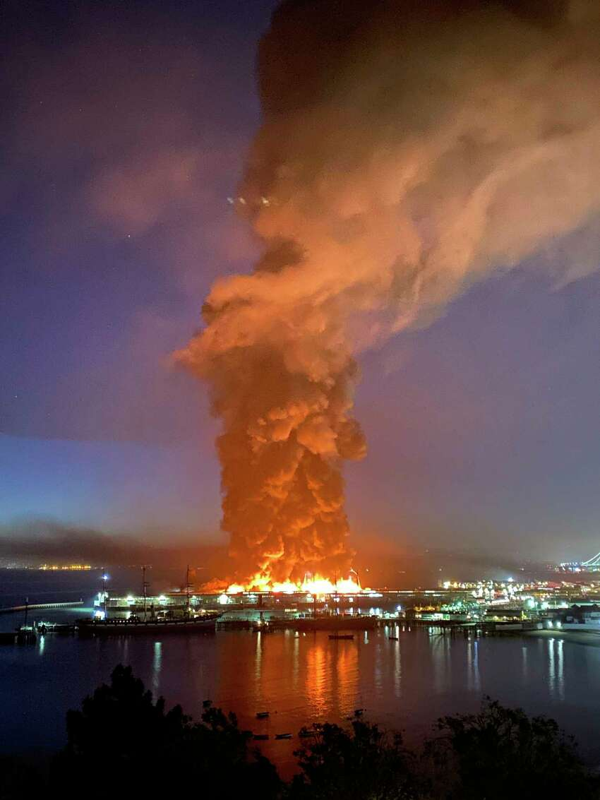 This photo courtesy of Dan Whaley, @dwhly, shows a warehouse fire burning at San Francisco's Fisherman's Wharf in San Francisco early Saturday, May 23, 2020. The fire tore through the warehouse, sending thick smoke over the waterfront and causing its walls to collapse. (Dan Whaley, @dwhly via AP)
