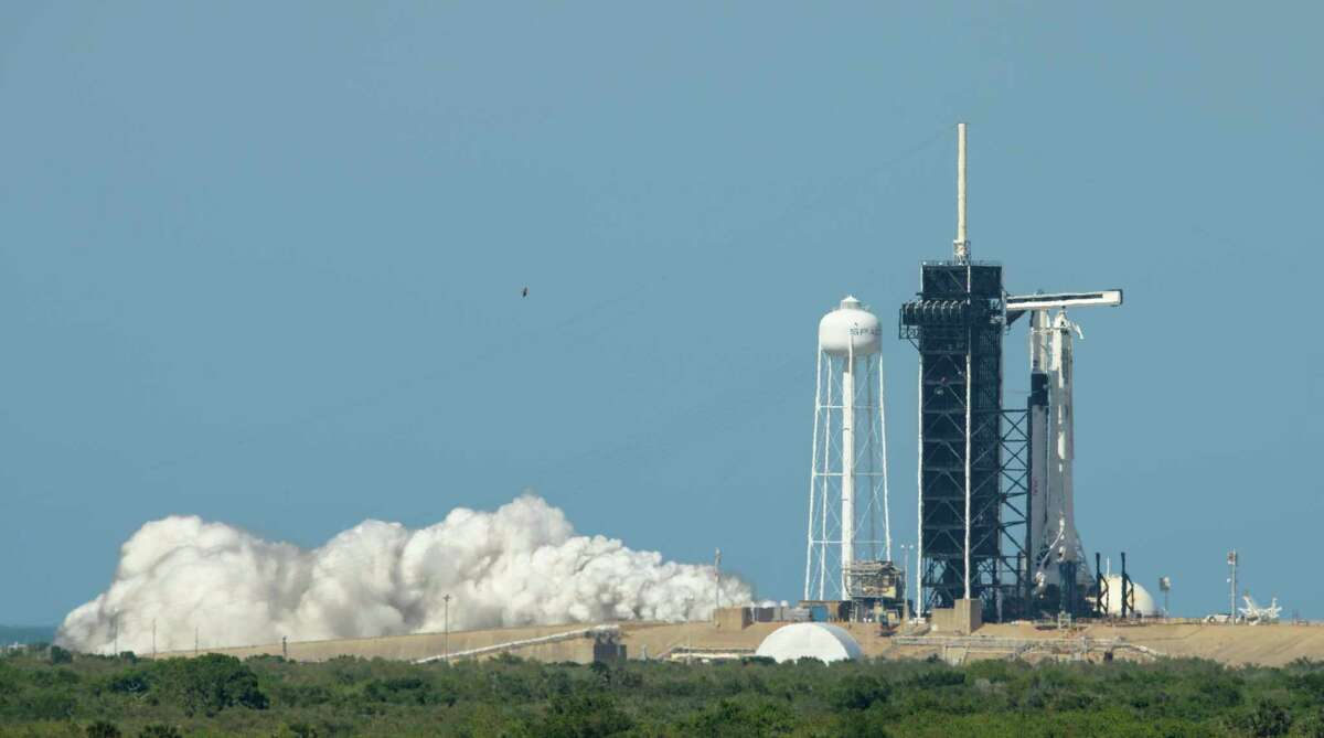 In this image provided by NASA, a SpaceX Falcon 9 rocket with the company's Crew Dragon spacecraft onboard is seen on the launch pad at Launch Complex 39A during a brief static fire test ahead of NASA's SpaceX Demo-2 mission, Friday, May 22, 2020, at NASA's Kennedy Space Center in Florida. (Bill Ingalls/NASA via AP)