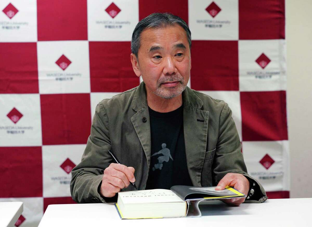 FILE - In this Nov. 3, 2018, file photo, Japanese novelist Haruki Murakami signs his autograph on his novel