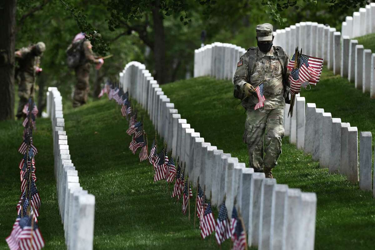 Soldiers place flags near headstones at Arlington National Cemetery in advance for Memorial Day on Thursday. MUST CREDIT: Washington Post photo by Matt McClain.