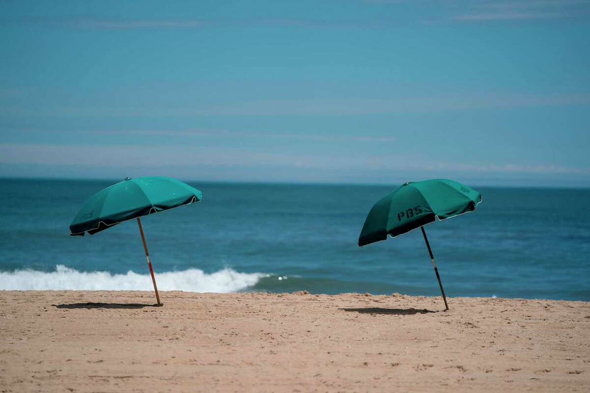 Sun umbrellas are seen on the beach amid the coronavirus pandemic during the Memorial Day holiday weekend on May 23, 2020 in Ocean City Maryland. - The beach front destination has lifted its COVID-19 related beach and boardwalk restrictions May 9 and lodging restrictions May 14. The state of Maryland moved from a stay-at-home order to safe-at-home order May 15. (Photo by Alex Edelman / AFP) (Photo by ALEX EDELMAN/AFP via Getty Images)