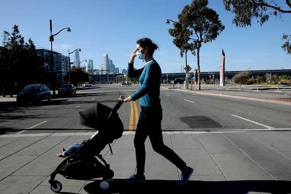 Allison Bond, a local infectious disease doctor, walks her 10-month-old son along Mission Bay Blvd. in San Francisco, Calif., on Saturday, May 23, 2020. San Francisco's health orders are long on specifics for businesses, but short on specifics for regular people.