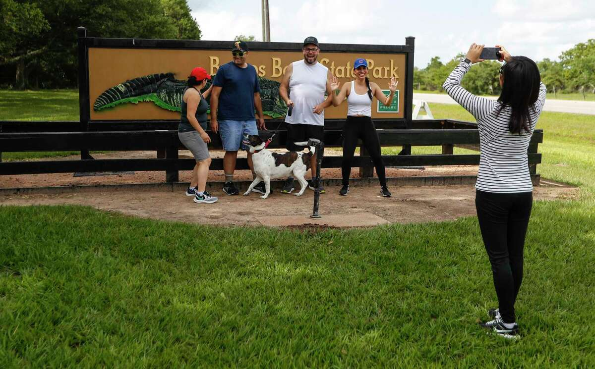 Le Huang takes a photo of her friends Maria Montes, Bha Vin Shah, Mike Van Alstine, and Martha Aguilar in front of the sign at Brazos Bend State Park, in Needville, Saturday, May 23, 2020. The group was unaware that the park was open by reservation only, but enjoyed a group photo by the sign. After two months in lockdown, parks are starting to open up during Memorial Day weekend. To book a weekend spot at Brazos Bend State Park, which is now limited to 40 percent capacity, the park superintendent reserving a day pass two to three weeks in advance. Other parks are sold out for the season.