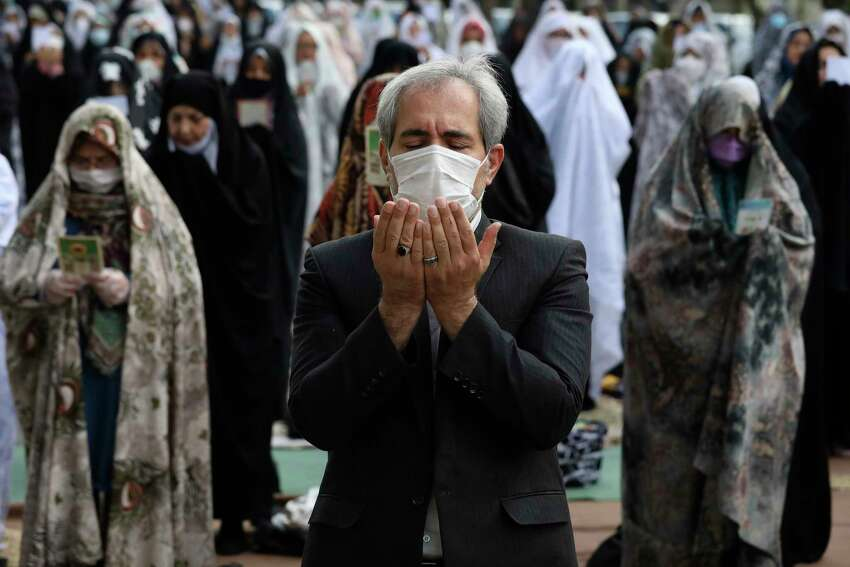 Worshippers wearing protective face masks offer Eid al-Fitr prayers outside a mosque to help prevent the spread of the coronavirus, in Tehran, Iran, Sunday, May 24, 2020. Muslims worldwide celebrate one of their biggest holidays under the long shadow of the coronavirus, with millions confined to their homes and others gripped by economic concerns during what is usually a festive time of shopping and celebration. In Iran, which has endured the deadliest outbreak in the Middle East, authorities have imposed few restrictions ahead of the holiday aside from cancelling mass prayers in Tehran traditionally led by Supreme Leader Ayatollah Ali Khamenei.